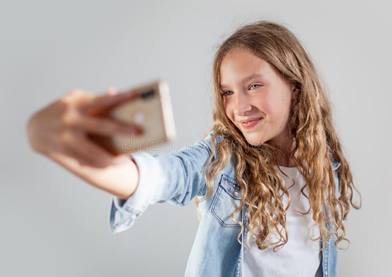Lächelndes jugendlich Herstellungsselfie Foto auf Smartphone über nettem Mädchen des weißen Hintergrundes stockbilder