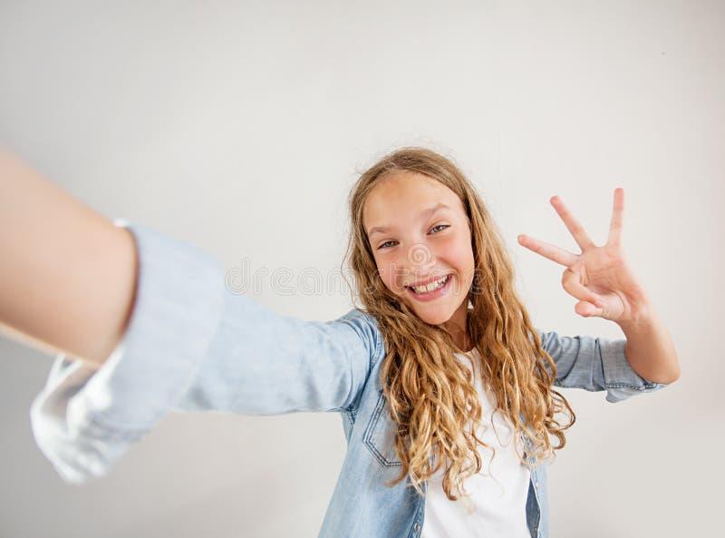 Lächelndes jugendlich Herstellungsselfie Foto auf Smartphone über nettem Mädchen des weißen Hintergrundes stockbild