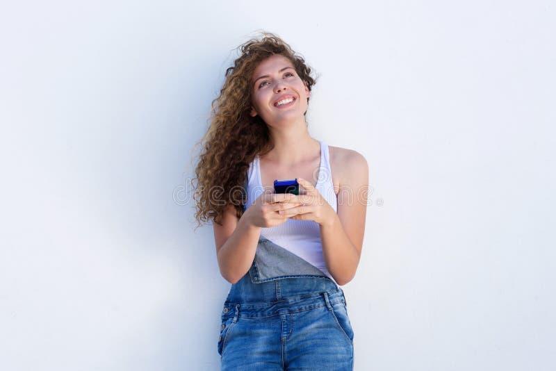 Lächelndes jugendlich intelligentes Telefon oben schauen und Halten lizenzfreies stockfoto