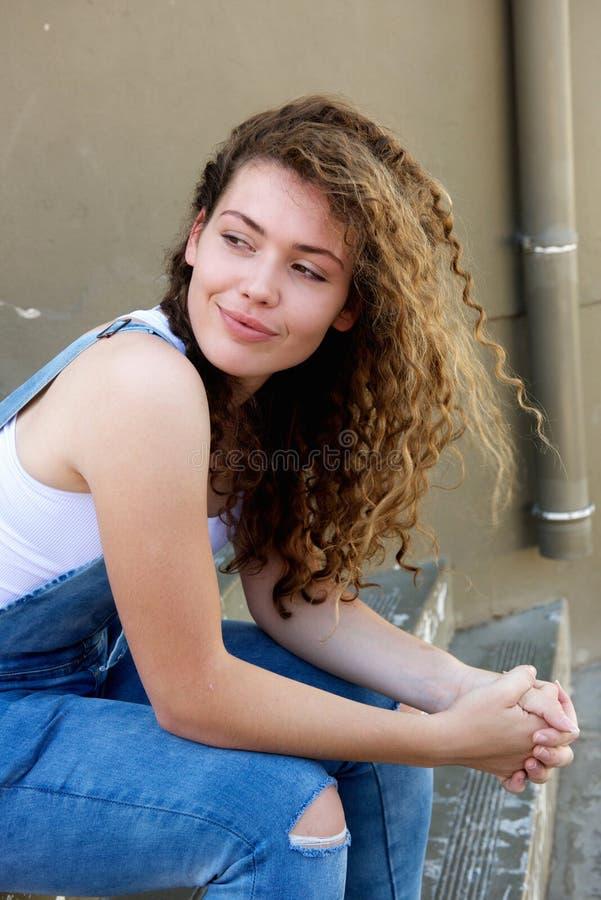 Lächelndes jugendlich Mädchen, das draußen auf Schritten sitzt stockfoto