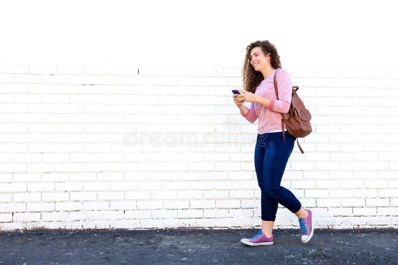 Lächelndes jugendlich Mädchen, das mit Mobiltelefon und Rucksack geht stockfoto