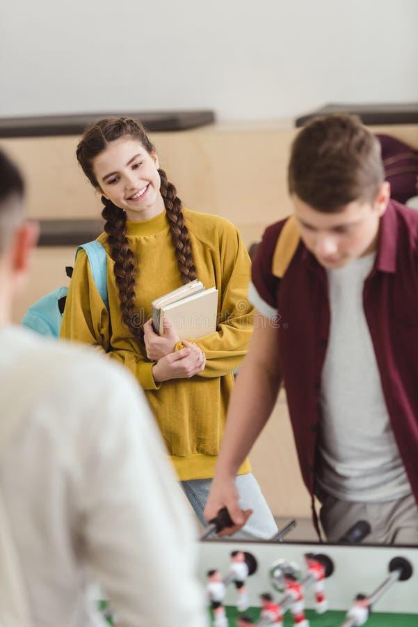 lächelndes Jugendschulmädchen, das mit Schüler spricht lizenzfreie stockbilder