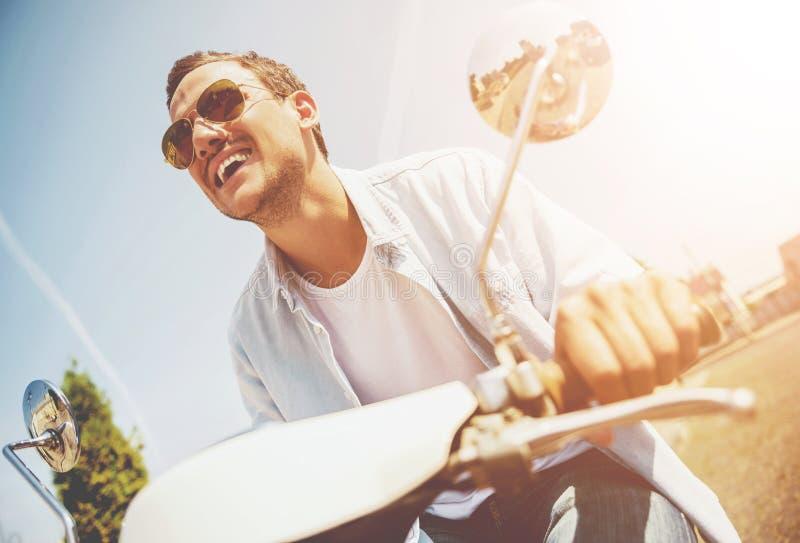 Lächelndes junger Mann-Reiten auf Roller entlang Straße lizenzfreies stockbild