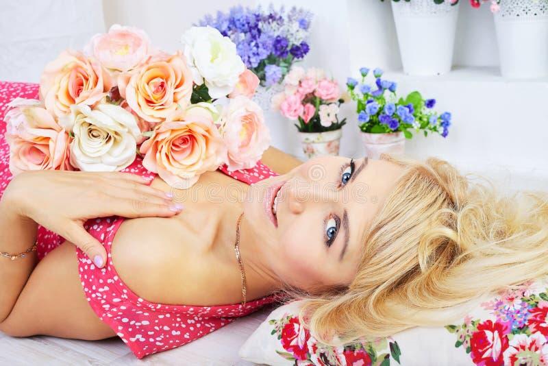 Lächelndes junges blondes Modell, das unter Blumen aufwirft stockbild