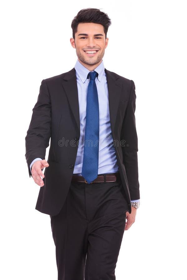 Lächelndes junges Geschäftsmanngehen lizenzfreie stockbilder