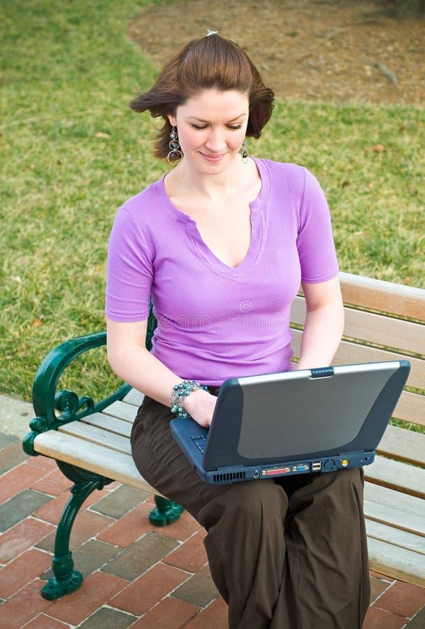 Lächelndes junges Kursteilnehmer-Mädchen mit Laptop-Technologie lizenzfreie stockbilder
