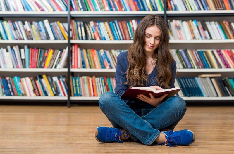 Lächelndes junges Mädchen, das auf dem Boden in der Bibliothek mit Kundenberaterinnen sitzt stockfotos