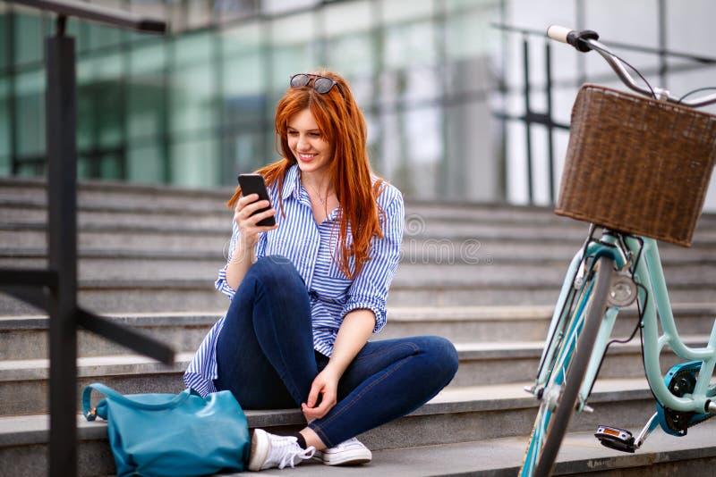 Lächelndes junges Mädchen, das auf Treppe und der Anwendung des Handys stillsteht stockbild