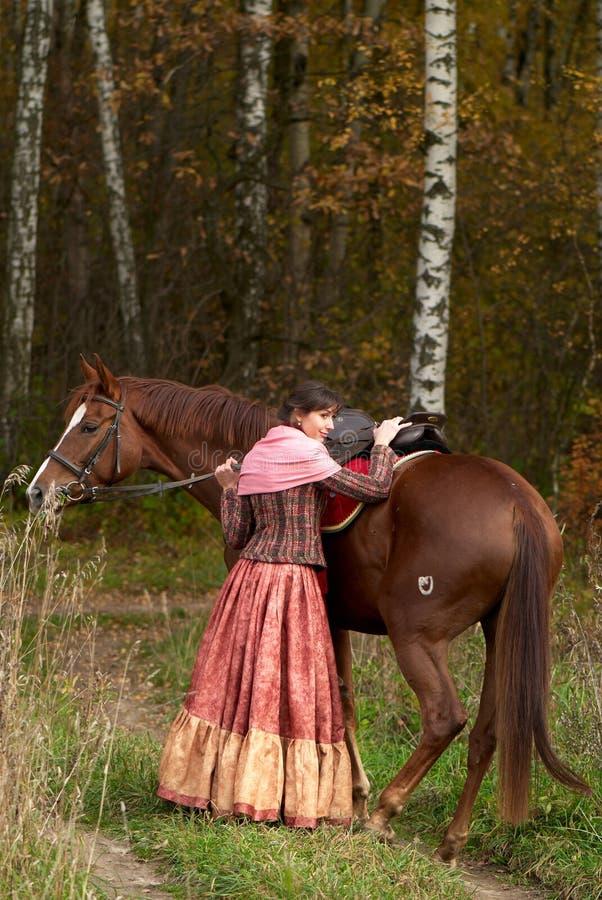 Lächelndes junges Mädchen, das ihr Pferd umarmt stockfotografie