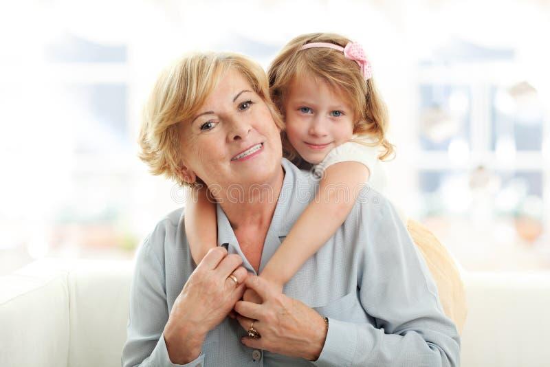 Lächelndes junges Mädchen, das ihre Großmutter umarmt stockfotos