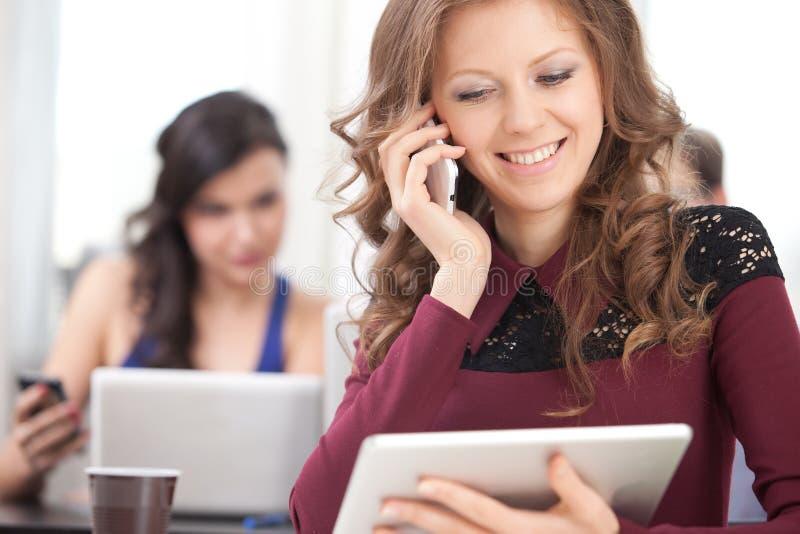Lächelndes junges Mädchen, das am Telefon spricht stockbilder