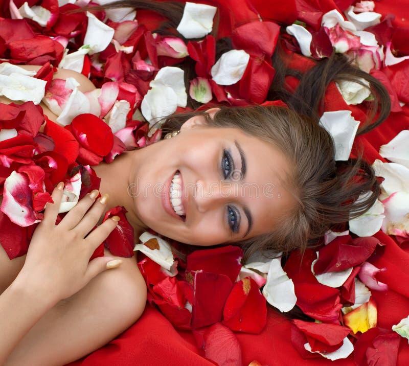 Lächelndes junges Mädchen im rosafarbenen Blumenblatt stockbilder