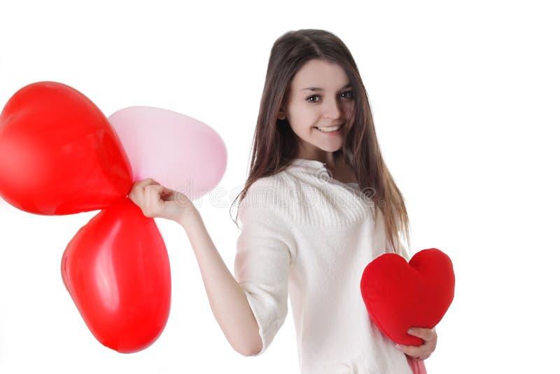 Lächelndes junges Mädchen mit Ballonen und Plüschherzen lizenzfreies stockbild