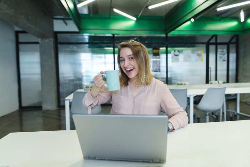 Lächelndes junges Mädchen mit einem Tasse Kaffee in ihren Armen, die am Schreibtisch im Büro und in der Anwendung eines Laptops s stockfoto