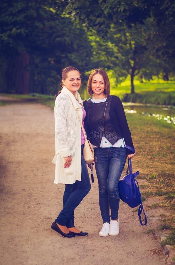 Lächelndes junges Mädchen zwei, das in einer Gasse im Park aufwirft lizenzfreies stockfoto
