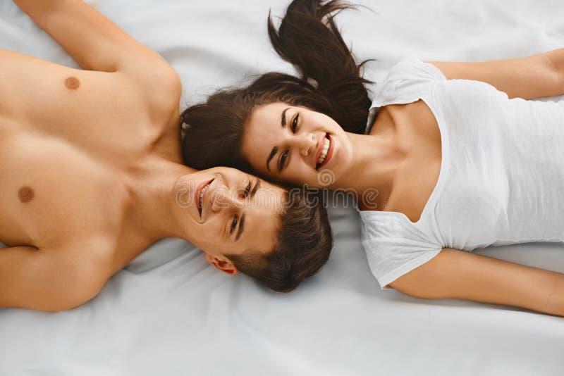Lächelndes junges Paarlügen stockbild