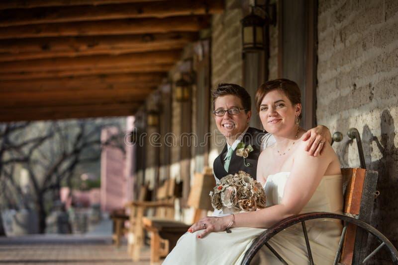 Lächelndes Jungvermählten-Sitzen stockfotos