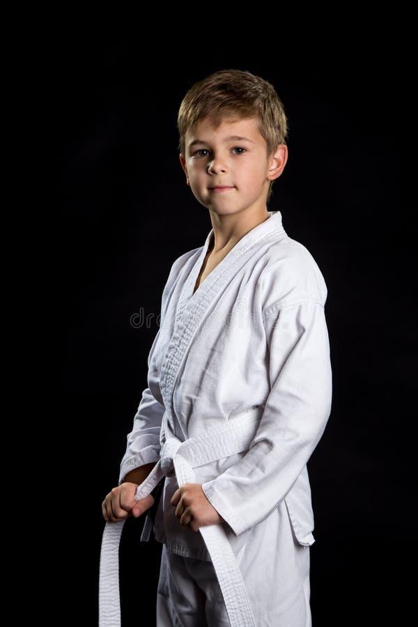 Lächelndes Karate scherzen im nagelneuen Kimono und werfen auf dem schwarzen Hintergrund auf Karatekämpfer, der seinen Gurt hält stockbild