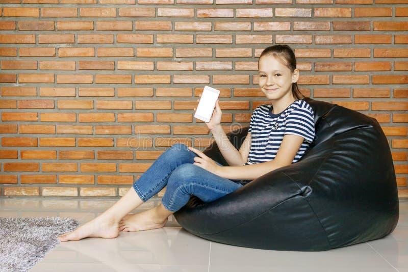 Lächelndes kaukasisches jugendlich Mädchen, das im Taschenstuhl der schwarzen Bohne gegen Backsteinmauer sitzt Zufällige Ausstatt stockbild