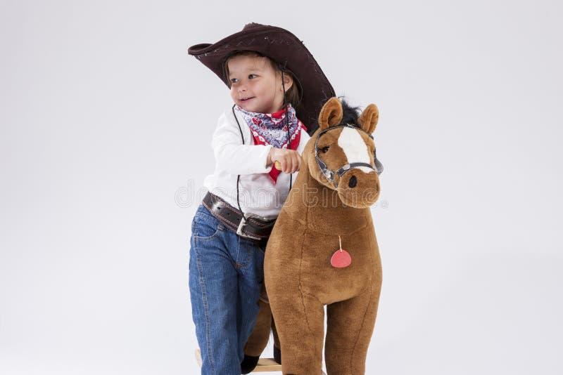 Lächelndes kaukasisches Mädchen in der Cowgirl-Kleidung, die mit symbolischem Plüsch-Pferd gegen Weiß aufwirft lizenzfreies stockbild
