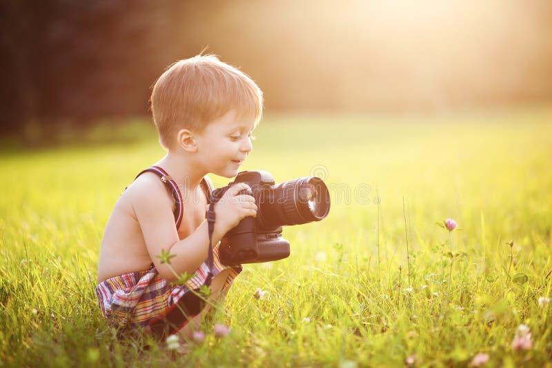 Lächelndes Kind, das eine DSLR-Kamera im Park hält stockfotografie