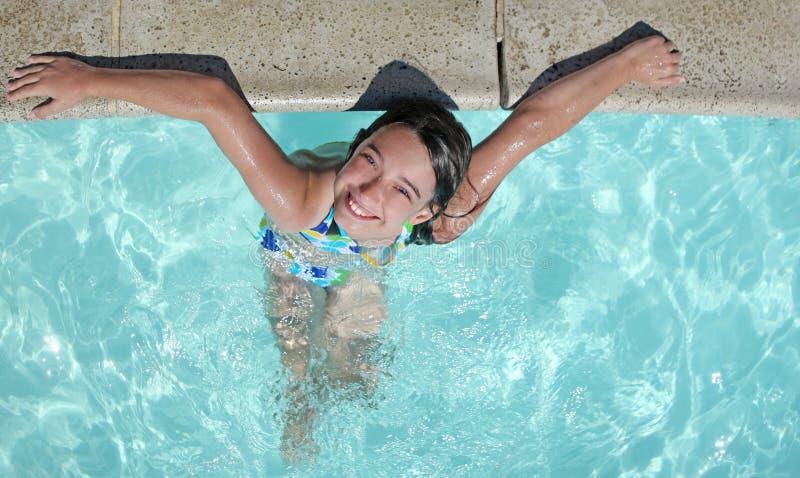 Lächelndes Kind, das in einem Swimmingpool sich entspannt lizenzfreie stockfotos