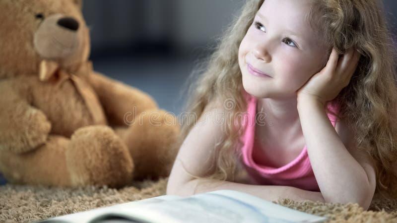L?chelndes Kind, das mit Gl?ck gl?nzt und, liegend auf Boden mit Buch tr?umerisch schaut stockfotos