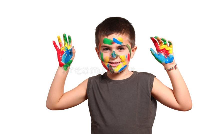 Lächelndes Kind, das seine farbigen Hände zeigt stockbilder