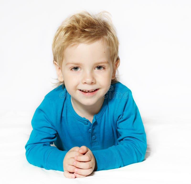 Lächelndes Kind, das sich, Kamera betrachtend hinlegt lizenzfreie stockfotografie