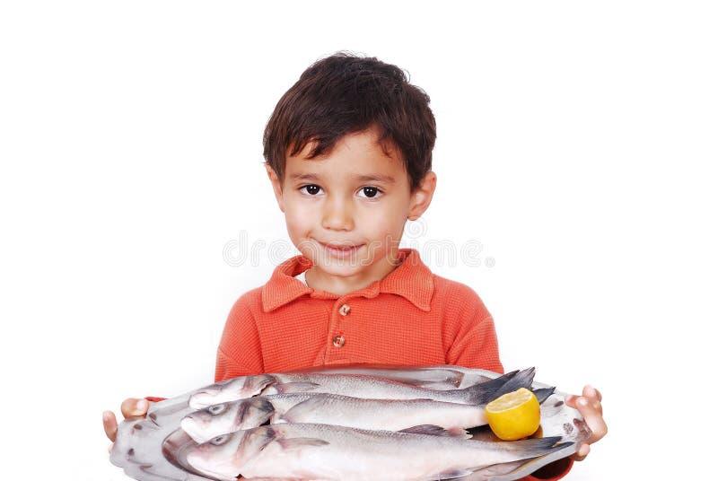 Lächelndes Kind mit drei frischen Fischen auf Tabelle lizenzfreie stockfotos