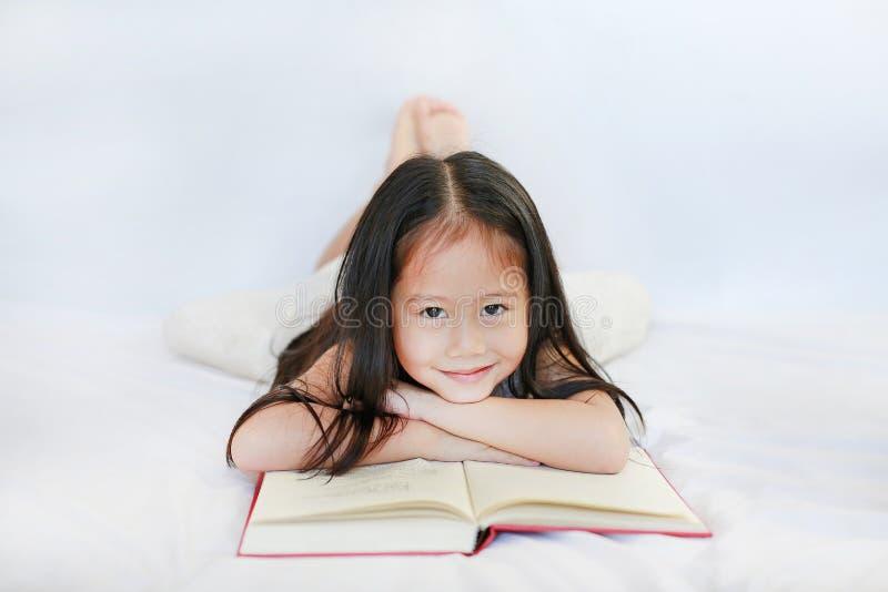 Lächelndes kleines asiatisches Kindermädchen mit dem gebundenen Buch, das auf Bett und dem Schauen der Kamera über weißem Hinterg stockbilder