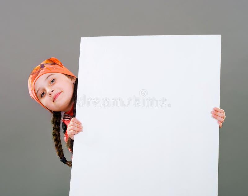 Lächelndes kleines Kind des jungen Mädchens im Herbstwinter kleidet den Jackenmantel und -hut, die ein weißes Brett der leeren An lizenzfreie stockfotografie