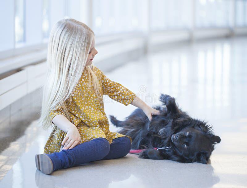 Lächelndes kleines Mädchen, das auf Boden und dem Tappen des schwarzen Hundes sitzt stockfotos