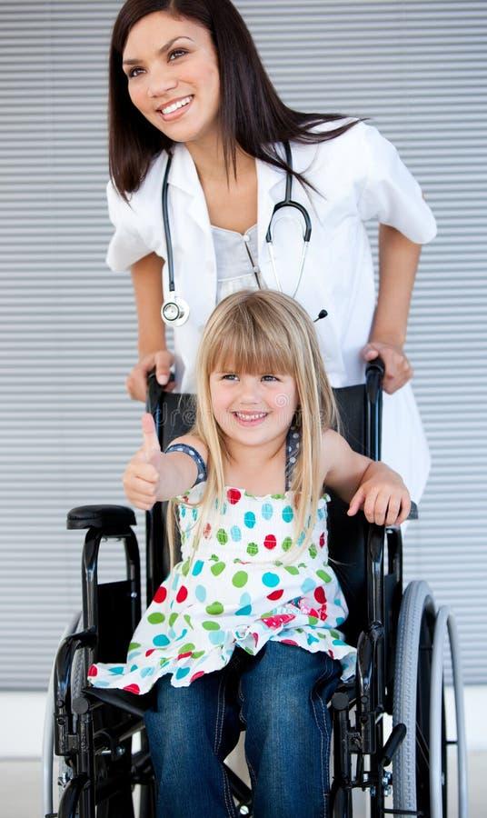 Lächelndes kleines Mädchen, das auf dem Rollstuhl sitzt stockfotografie