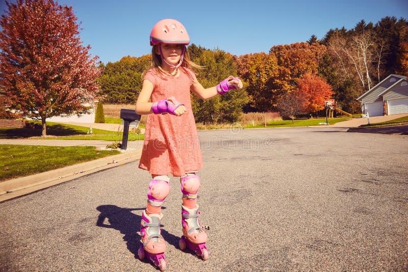 Lächelndes kleines Mädchen, das auf Rollschuhen steht lizenzfreies stockfoto
