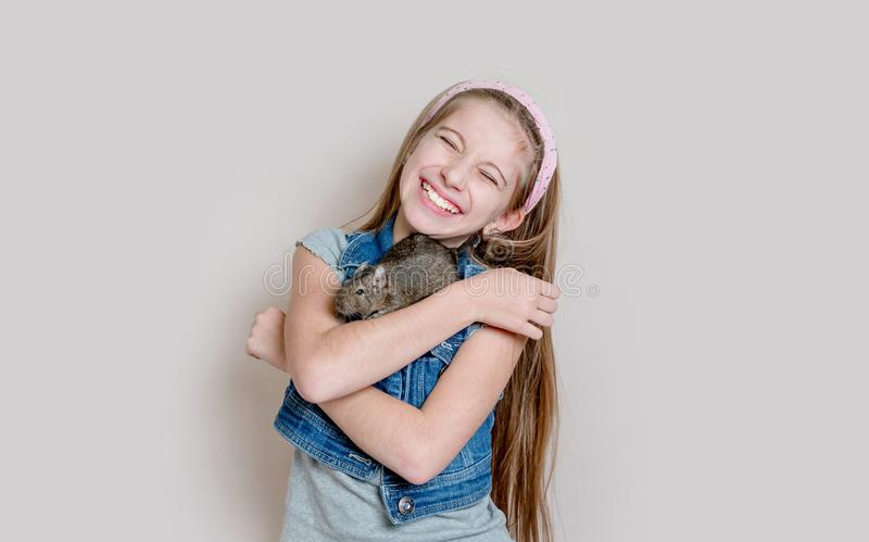 Lächelndes kleines Mädchen, das ein degu auf ihren Armen hält lizenzfreie stockfotografie