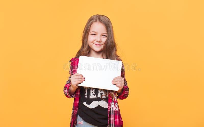 Lächelndes kleines Mädchen, das einen leeren Tablet-Computer hält stockbilder