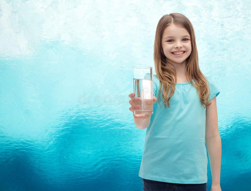 Lächelndes kleines Mädchen, das Glas Wasser gibt lizenzfreies stockfoto