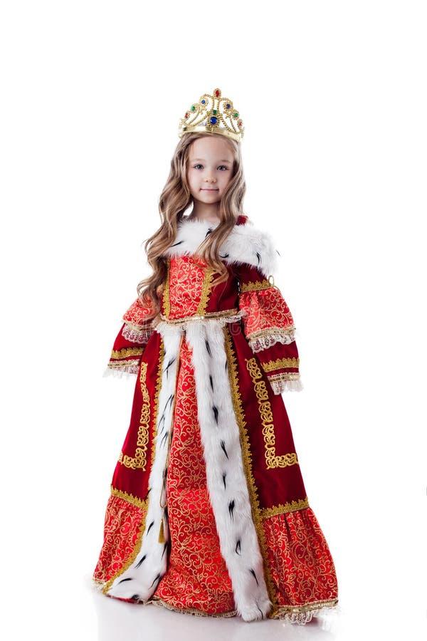 Lächelndes kleines Mädchen, das im königlichen Kleid aufwirft stockbild