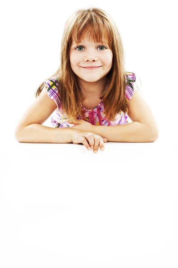 Lächelndes kleines Mädchen, das leeren weißen Vorstand anhält lizenzfreie stockfotos