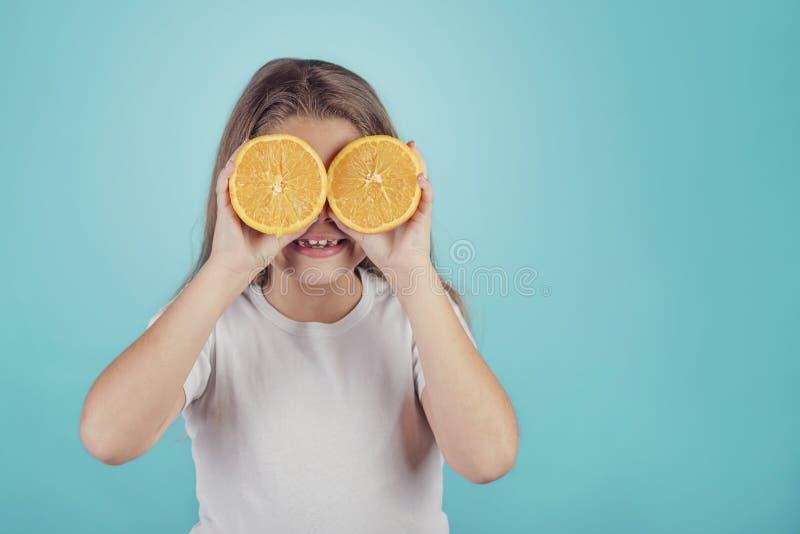Lächelndes kleines Mädchen, das Orangen über ihren Augen hält lizenzfreies stockfoto