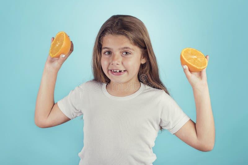 Lächelndes kleines Mädchen, das Orangen hält lizenzfreie stockbilder