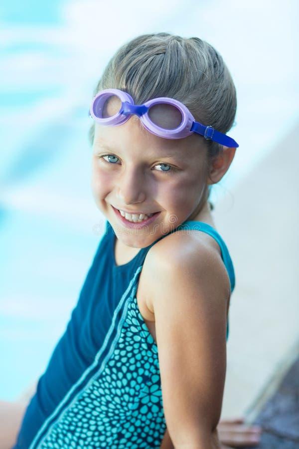 Lächelndes kleines Mädchen, das am Poolside sitzt lizenzfreie stockfotos