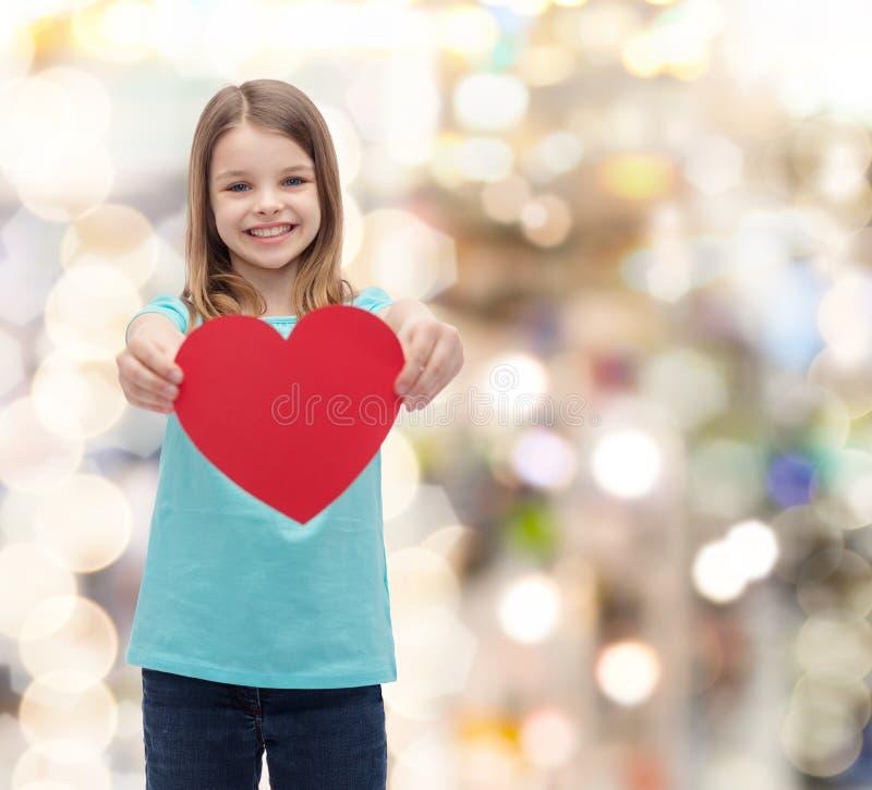 Lächelndes kleines Mädchen, das rotes Herz gibt lizenzfreie stockbilder