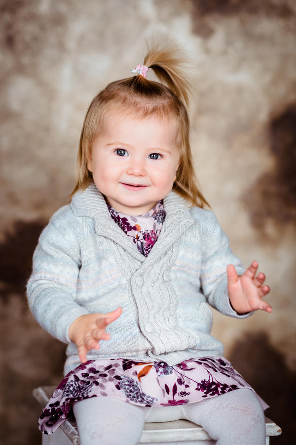 Lächelndes kleines Mädchen des Bonbons mit dem blonden Haar, das auf Stuhl sitzt lizenzfreies stockfoto