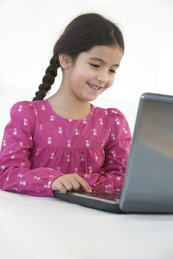Lächelndes kleines Mädchen hinter einem Laptop lizenzfreie stockfotografie