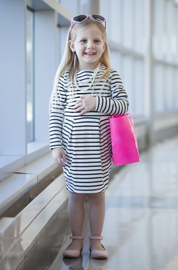 Lächelndes kleines Mädchen im Weiß streifte Kleid mit Einkaufstasche lizenzfreies stockfoto