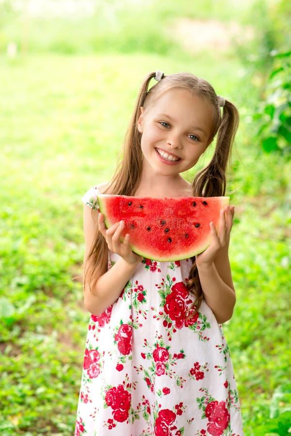 Lächelndes kleines Mädchen mit blauen Augen isst eine Scheibe der Wassermelone stockbilder