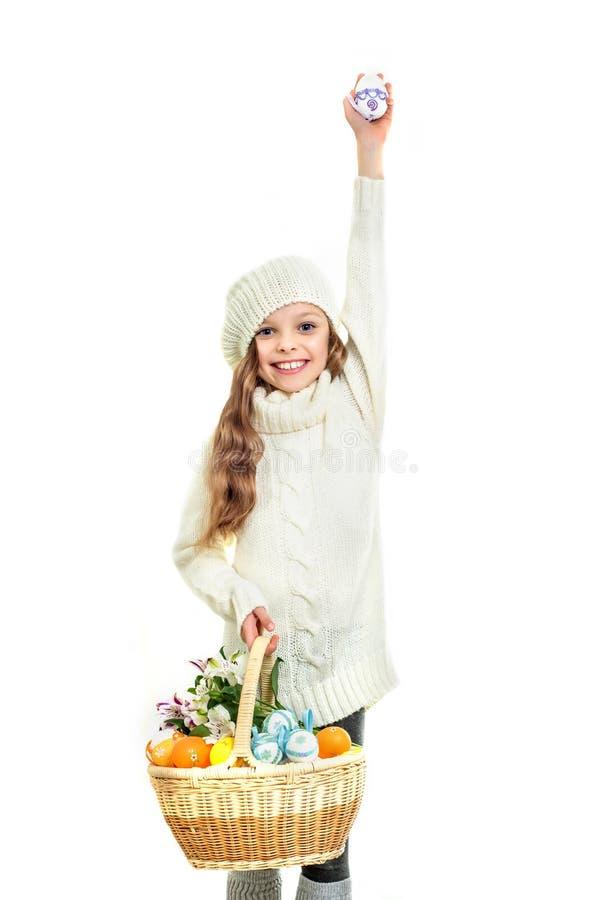 Lächelndes kleines Mädchen mit dem Korb voll von bunten Ostereiern stockfotos