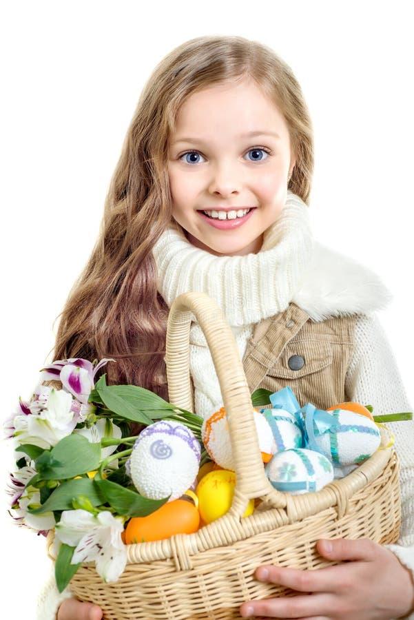 Lächelndes kleines Mädchen mit dem Korb voll von bunten Ostereiern lizenzfreie stockfotografie
